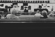 elderly women talking to each other in the pews at church