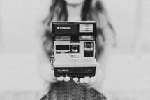 Woman holding Polaroid camera
