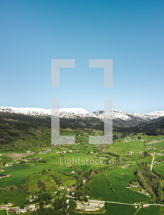 aerial view over a green valley surrounded by snow capped mountains