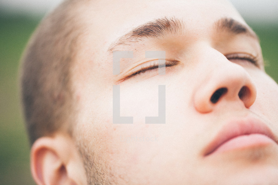 close-up of the closed-eyes and face of a man worshiping God