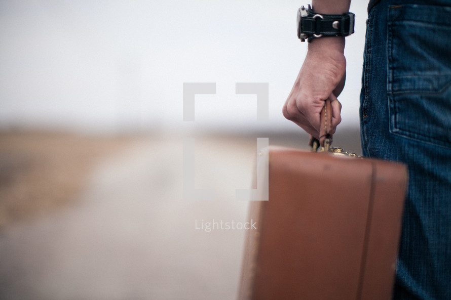 close-up of a man holding a suitcase looking down a road