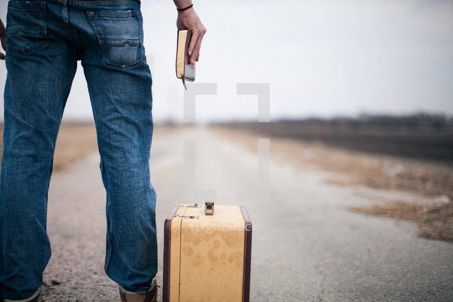 man holding a Bible standing next to a suitcase looking down a long road