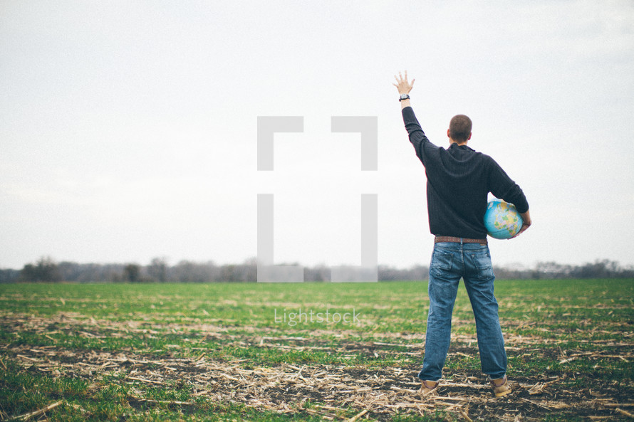 man holding a globe standing in a field with his hand raised in worship