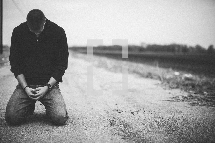 man kneeling in prayer in the middle of a rural road
