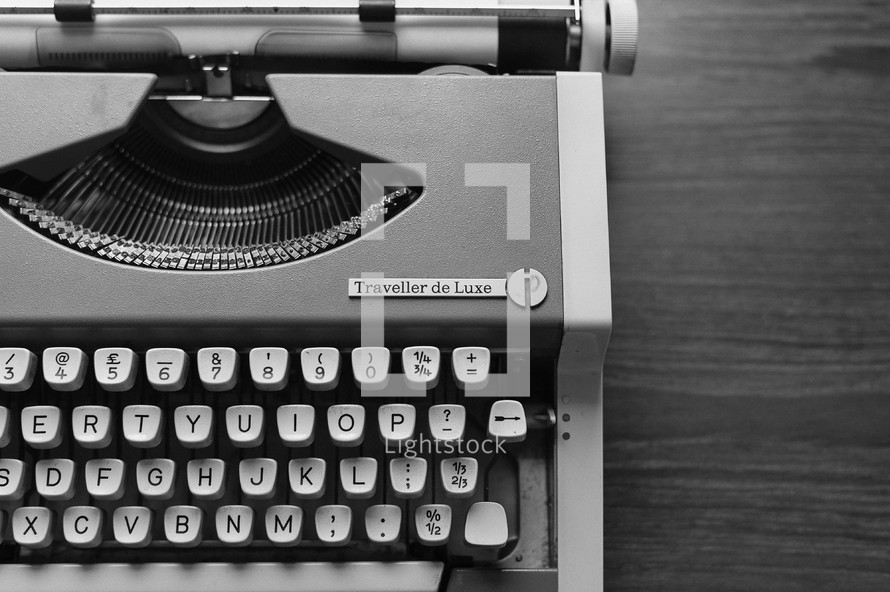 A black-and-white version of the old orange typewriter in this series. Close-up of keys, on wood backdrop.