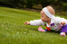 Infant girl picking flowers in the grass