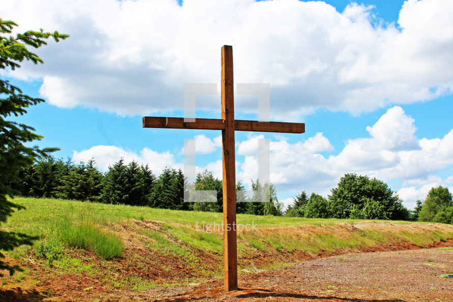 A large wooden cross in the countryside.
