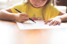 A young girl drawing on paper.