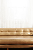 gold leather couch in front of a window.