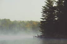 Morning mist over a lake with large pine trees. Dock and Muskoka chairs.