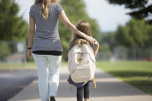 a young girl holding hands with mom while walking to school.