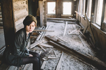 A woman sitting in an unfinished log house.