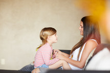 a mother and daughter sitting together talking on the couch