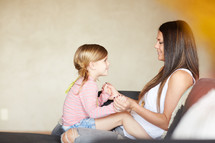 a mother and daughter sitting together on a couch