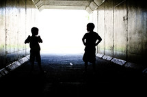 Silhouette of children playing in a tunnel.