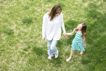 mother and daughter walking holding hands through grass