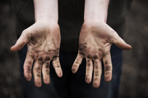 Man showing his dirty hands.