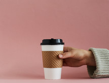 a hand reaching for a coffee cup