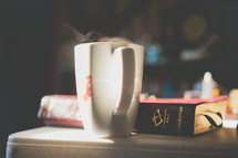 steam from a coffee mug and a Bible on a table
