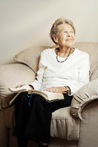 Smiling elderly woman sitting on the couch reading the Bible.