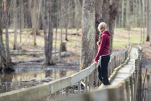 A young woman alone on a pedestrian bridge in a wooded area.