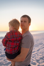 a father holding his son on a beach