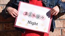 A little girl holding a Bingo Night sign