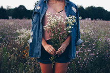 a woman walking through a field picking flowers