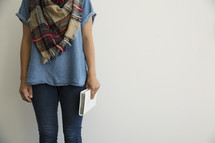 a woman in jeans and a plaid shaw holding a Bible at her side