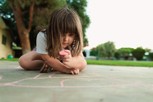 a girl child coloring with sidewalk chalk