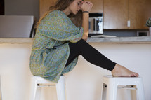 a woman in her pajamas praying in the kitchen