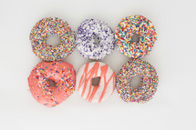 rows of sprinkled donuts on a white background