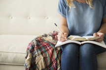 a woman reading a Bible and writing in a journal sitting on a couch