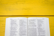 pages of an open Bible on a yellow table