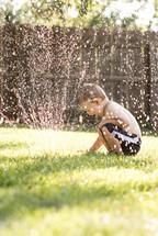 boy child playing in a sprinkler