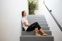 a tired woman sitting on steps