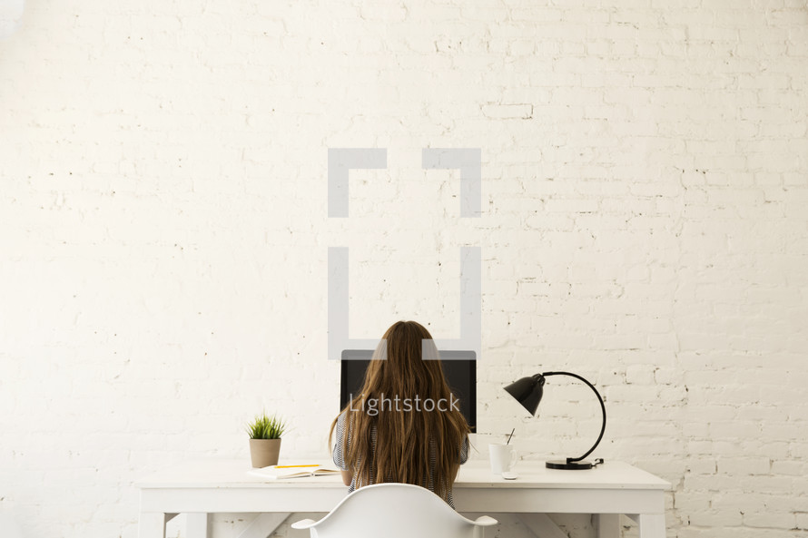 a woman sitting at a desk working at a computer
