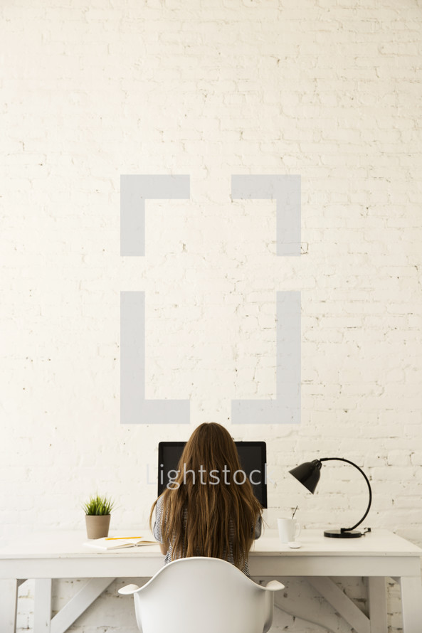 woman sitting at a desk working at a computer
