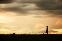 silhouette of a woman walking her dog at sunset