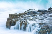 water flowing over a rock cliff