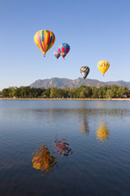 Colorful Hot air balloons flying over a Colorado Lake with the mountains in the distance