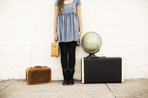 woman holding a suitcase and standing next to a globe