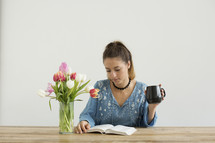 a woman sitting at a desk with a mug of coffee and a vase of tulips