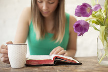 Woman with a coffee cup  reading the Bible on a wood table with tulips.