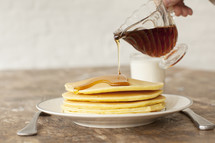 Pouring syrup on a stack of pancakes.