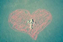 Ashes in the shape of a cross in a pink chalk drawn heart  - Ash Wednesday and Valentine's Day February 14, 2018