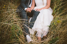 bride and groom sitting in a field