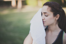 Woman wiping the sweat from her face with a towel.