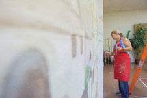 a woman painting a mural on a wall