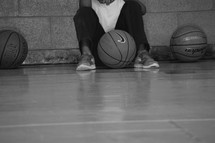 An African American boy waiting on the sidelines of a basketball court
